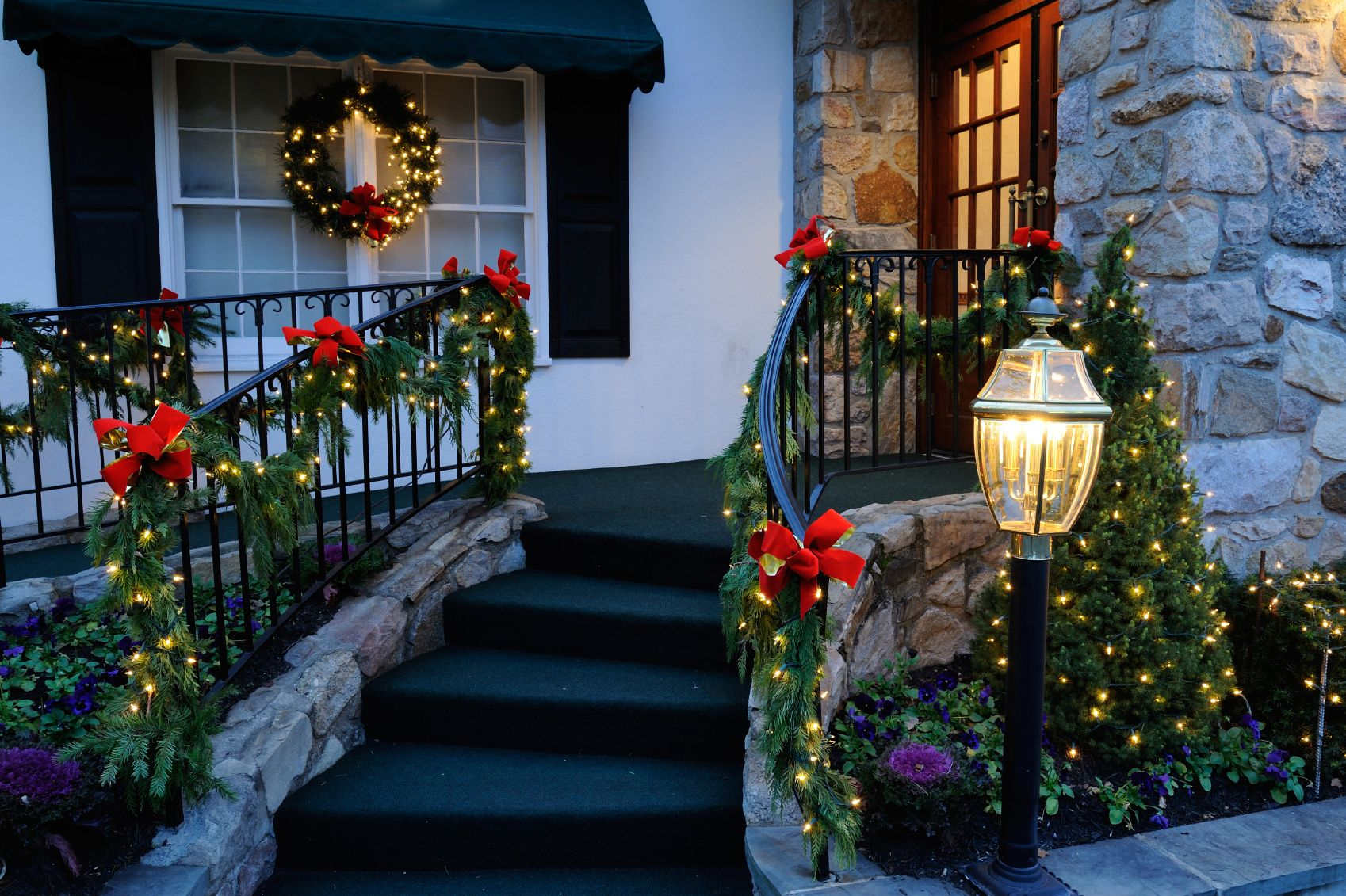 Lighted Garland And Red Bows Create A Clic Christmas Porch