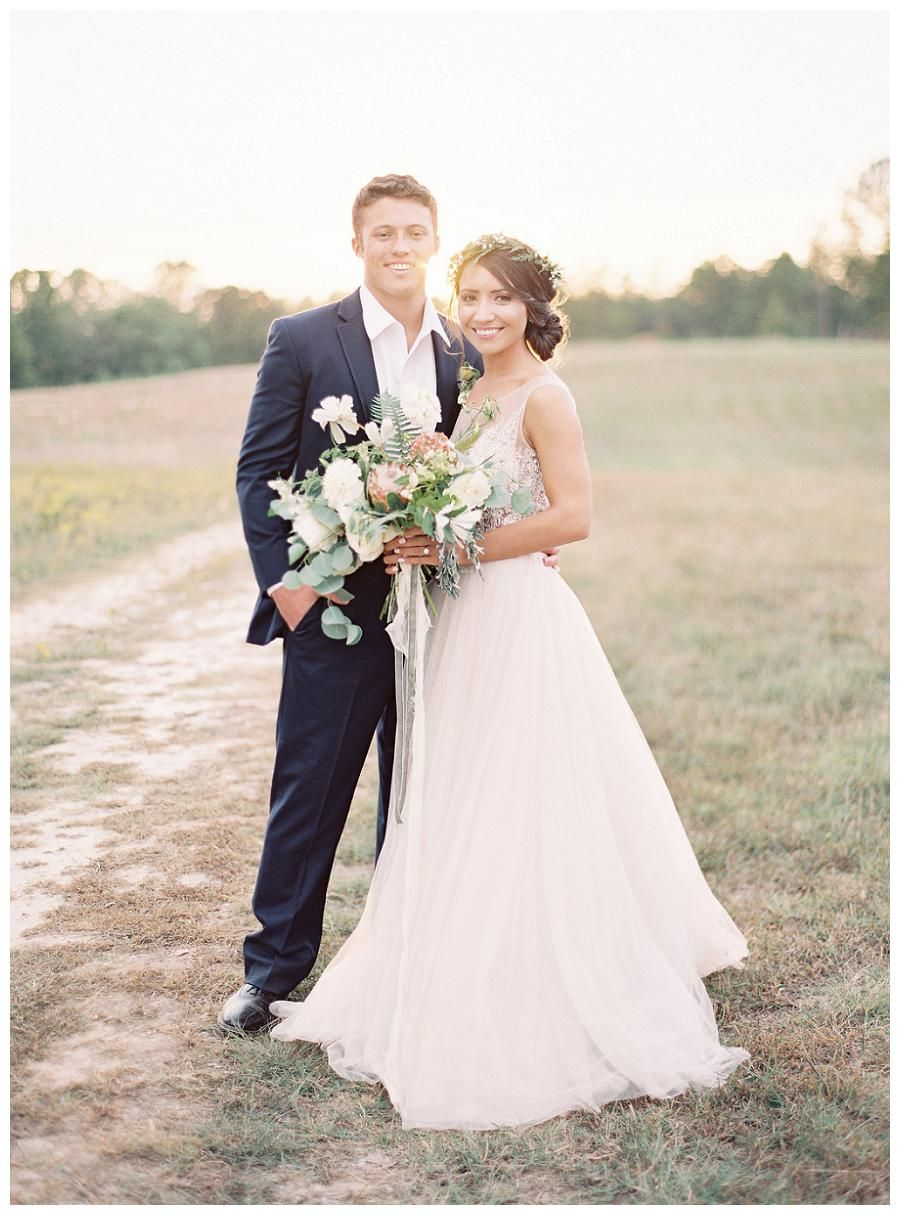 Bride and groom on a country road. Bridal bouquet by