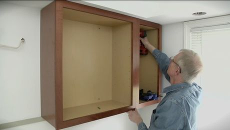 Installing upper cabinets begins with attaching a level cleat to the ...