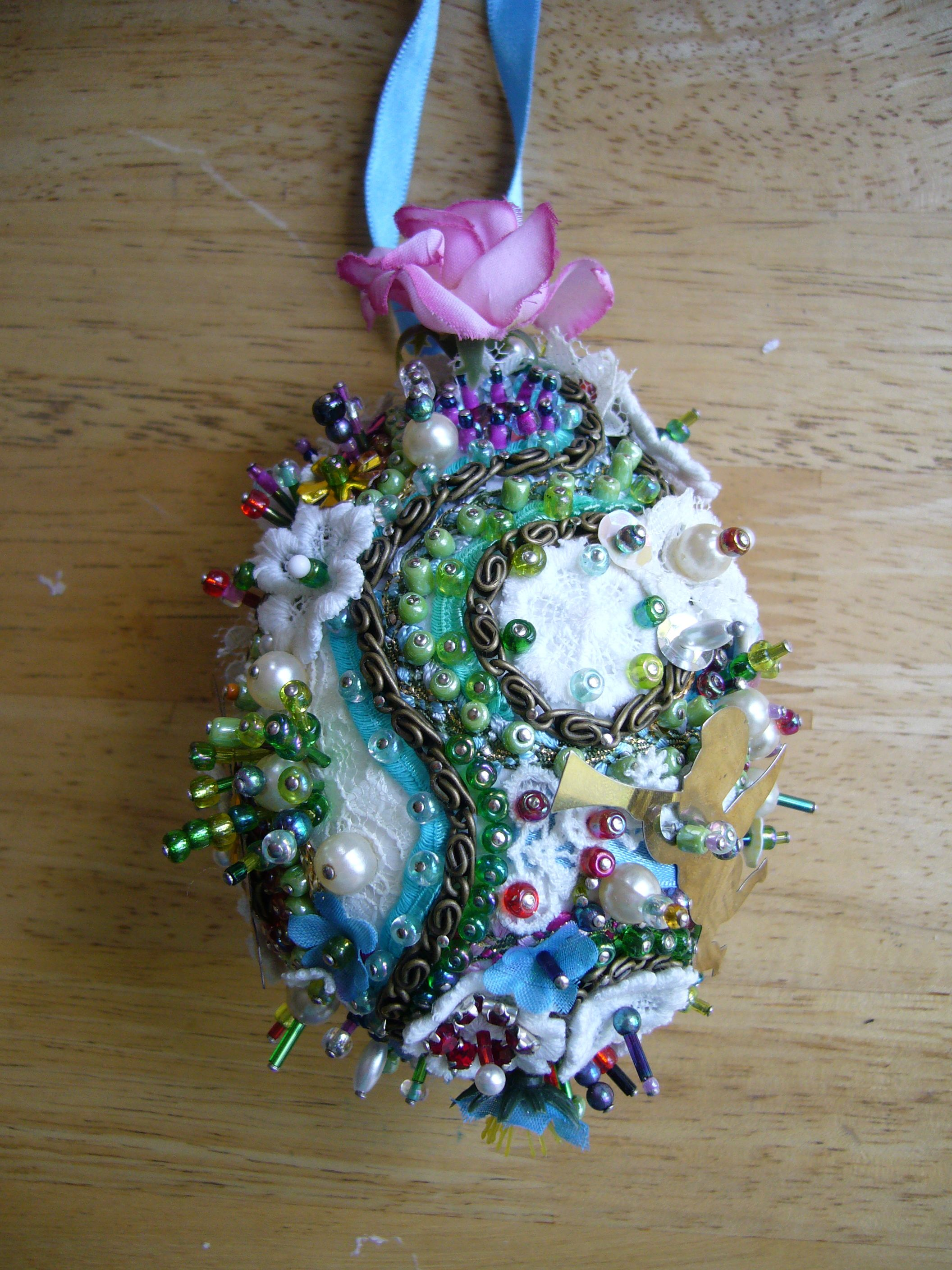 A polystyrene egg decorated in ribbon, lace and beads all held on with pins