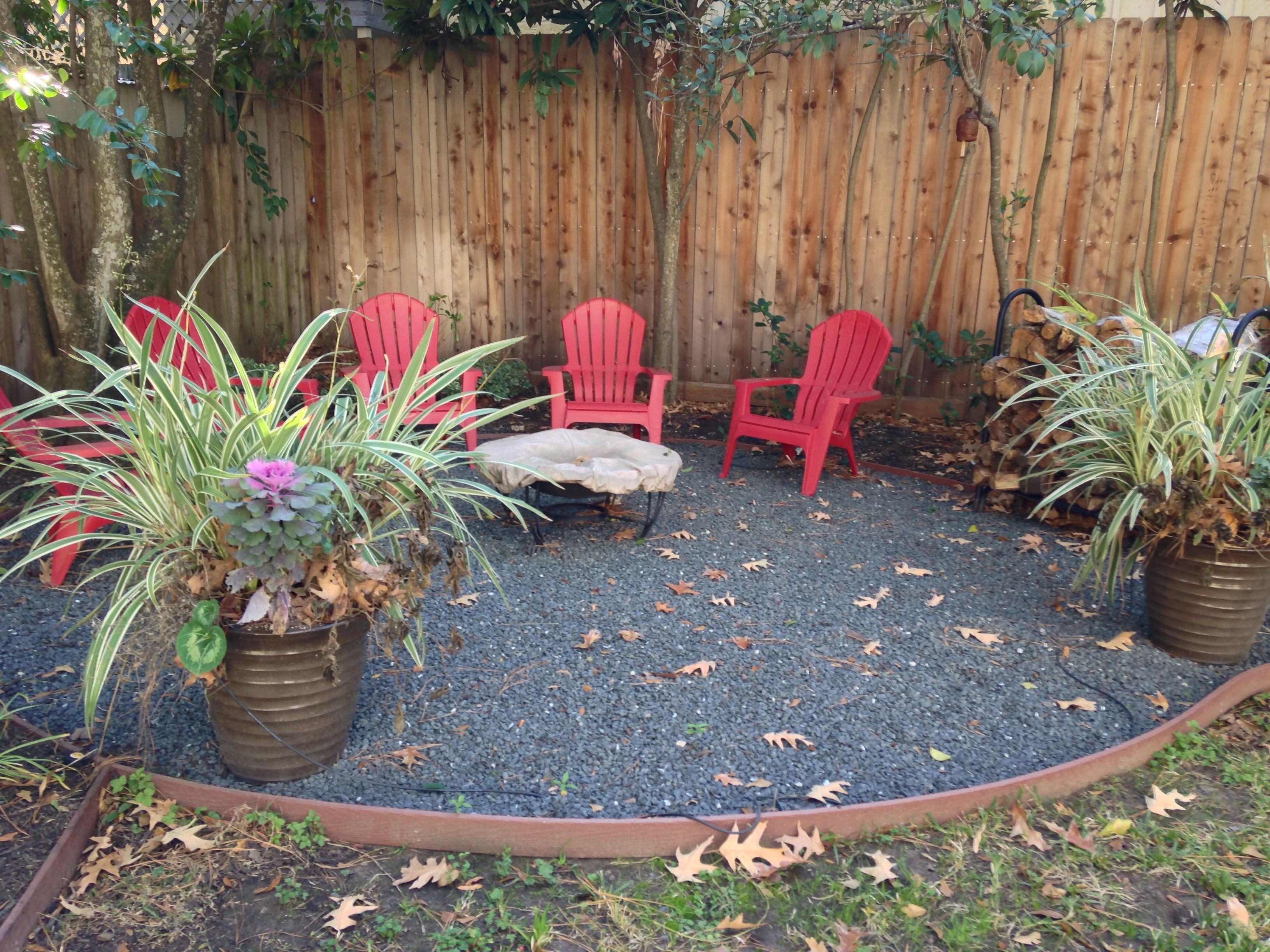 Clear an area and fill with rocks/gravel, chairs and a couple large planters. Love the stone table!