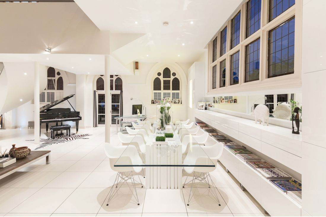 Glass dining table bright white interior church conversion in london england