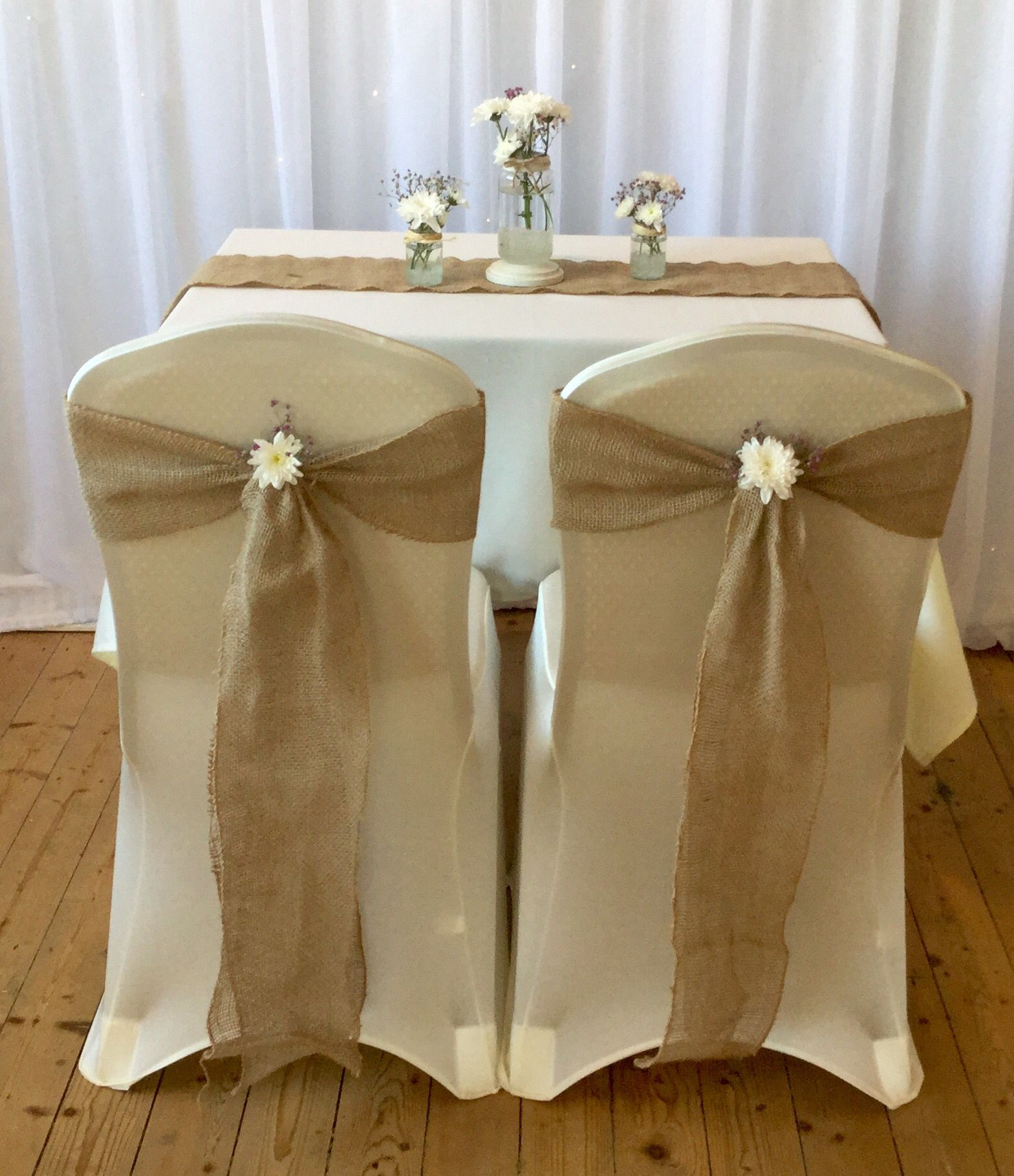 These Beautiful Ivory Chair Covers Being Complimented With Hessian Sashes And Flowers To Give A Rustic Sim Chair Covers Wedding Wedding Ceiling Wedding Chairs