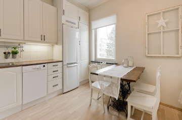 Kauniissa vaaleassa keittiössä on antiikkisen ruokapöydän päälle ripustettu maalaisromanttiset ikkunankarmit