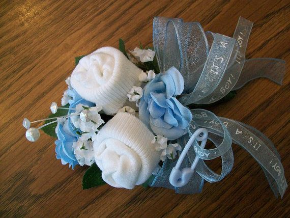 Mothers Corsage for baby shower! ITS A BOY!    This corsage contains 1 pair of white socks, baby blue roses surrounded by green leaves, babys