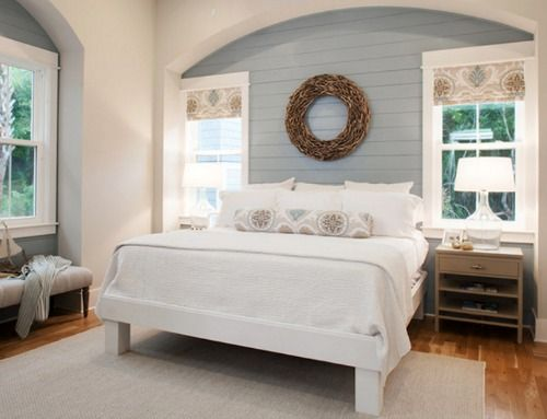 Shiplap accent wall in a bedroom painted gray with driftwood wreath above the bed