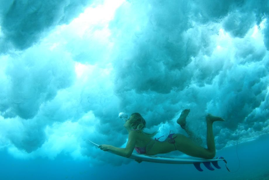 Under water view of surfer girl ducking under a breaking w