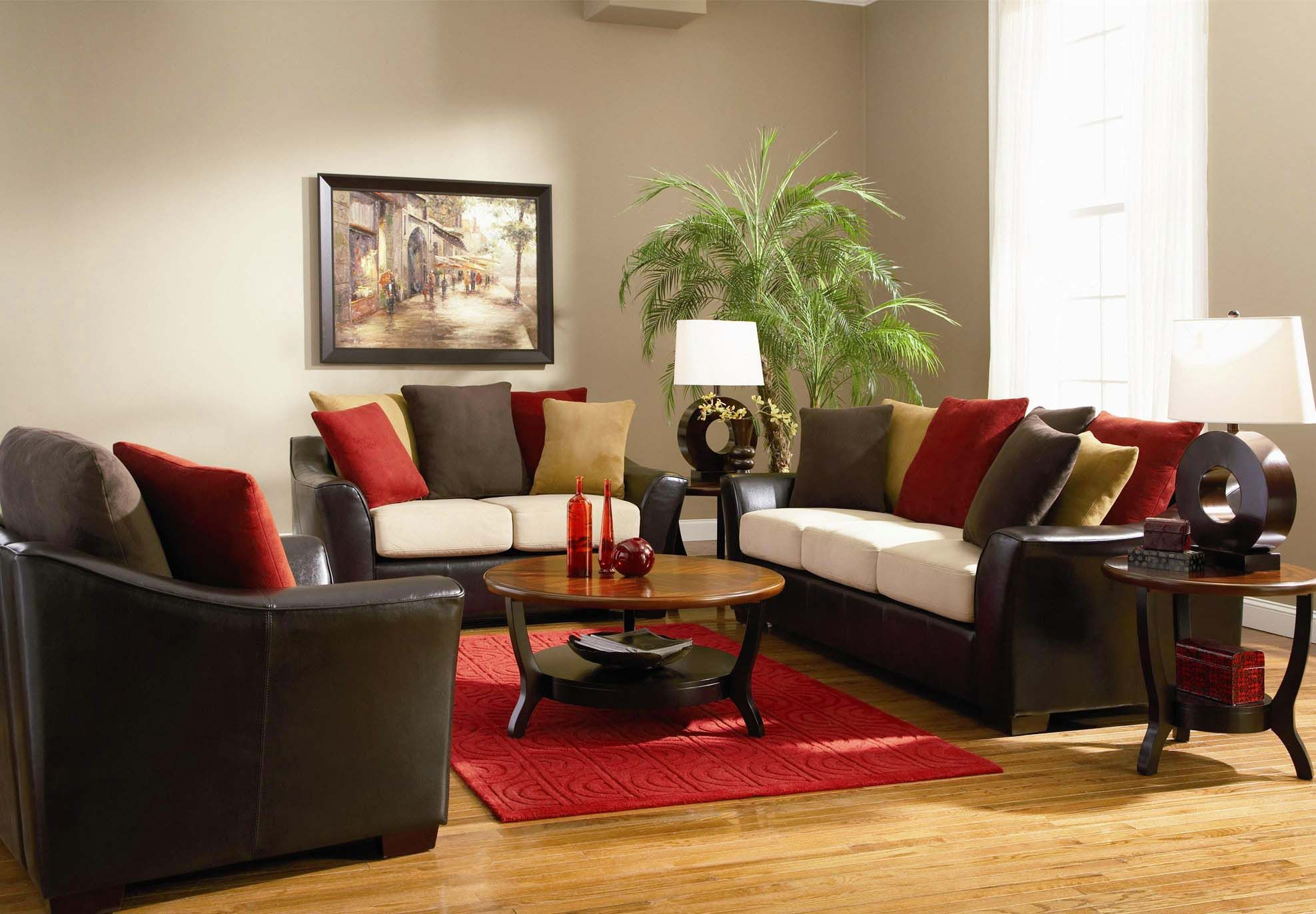 Round Dark Brown Wooden Table Beside Black Leathr Sofa And Various Color Cushions Plus Red Rug With Narrow Tables
