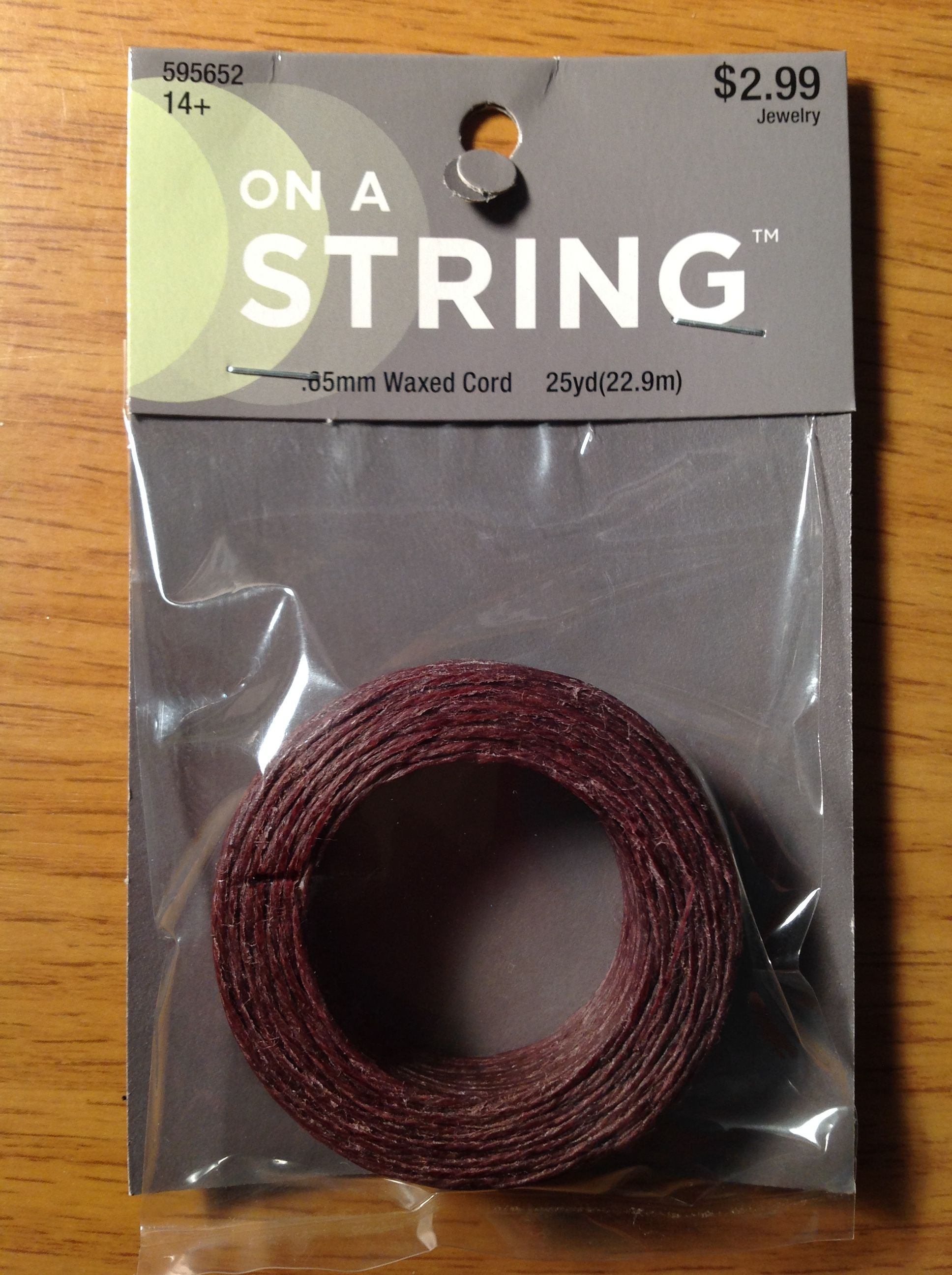 On a String .65mm Waxed Cord - Brown.  25 yds.  Hobby Lobby 11/12/2016  $1.49 ($1.57 = ~ $0.0025/in.)