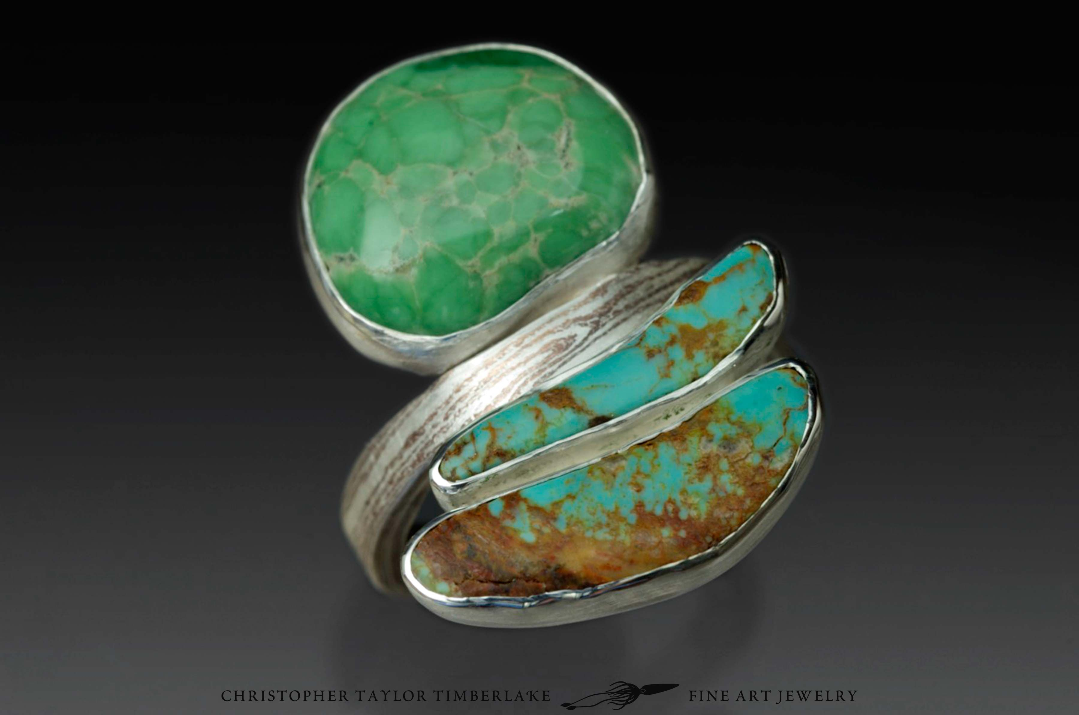 This unique ring features two bezel set cabochons of turquoise and variscite. The 3 mm wide mokumé shank is composed of sterling silver and copper.