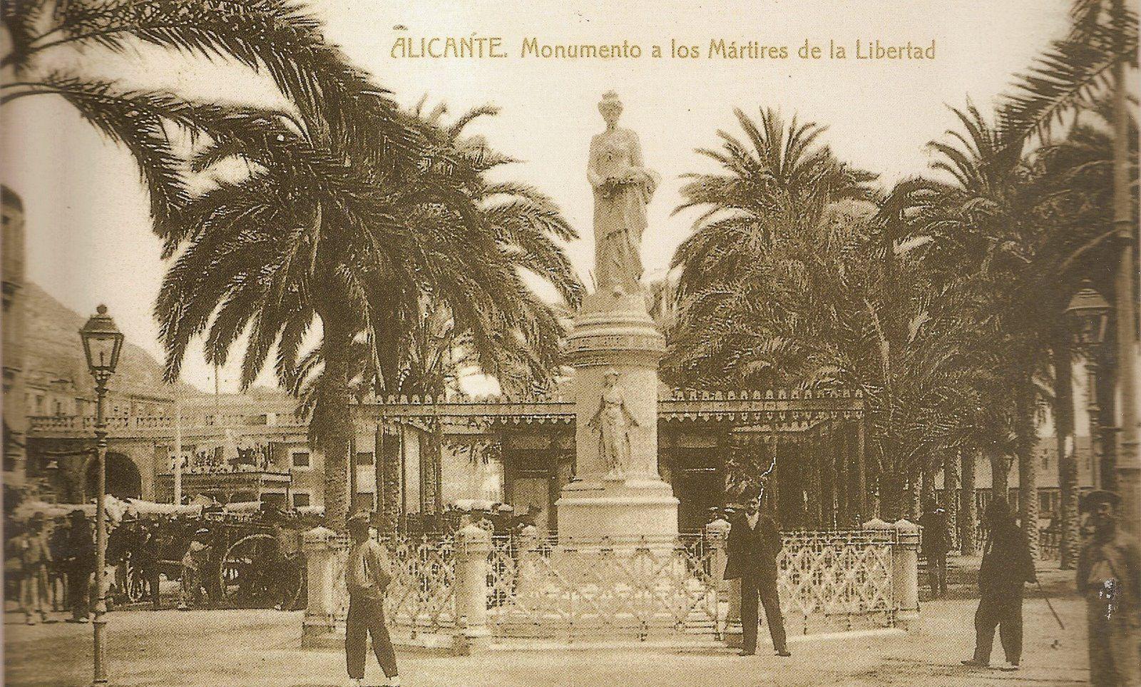 El Monumento a los Mártires de la Libertad situado dentro de la Explanada, frente a la Calle del Triunfo (hoy Alberola Romero). A la izquierda puede verse el antiguo Mercado Central. La Explanada, desde aquí, continuaba con sólo dos hileras de palmeras.