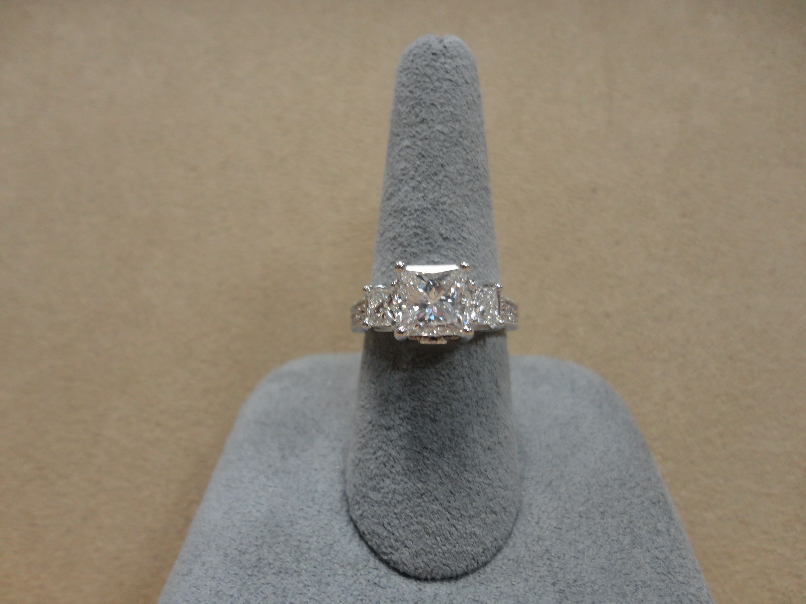 Cushion cut center stone with princess cut side stones set in a