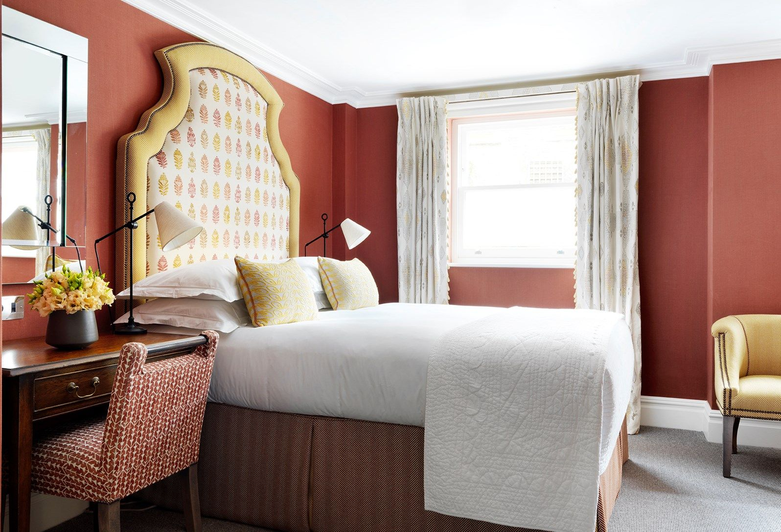A bright and light bedroom containing an inviting bed with