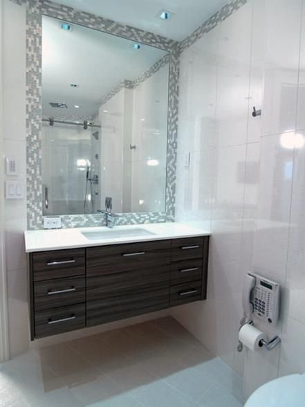 """Despite its small size, this contemporary floating vanity designed by Anna Marie Fanelli packs plenty of clever storage. The vanity's large center drawer houses a custom laundry hamper, while the drawers on the left feature dividers for easily organized creams, toothbrushes and more. """"A hanging vanity makes the space appear larger, and makes it easy to clean the space,"""" Anna Marie says."""
