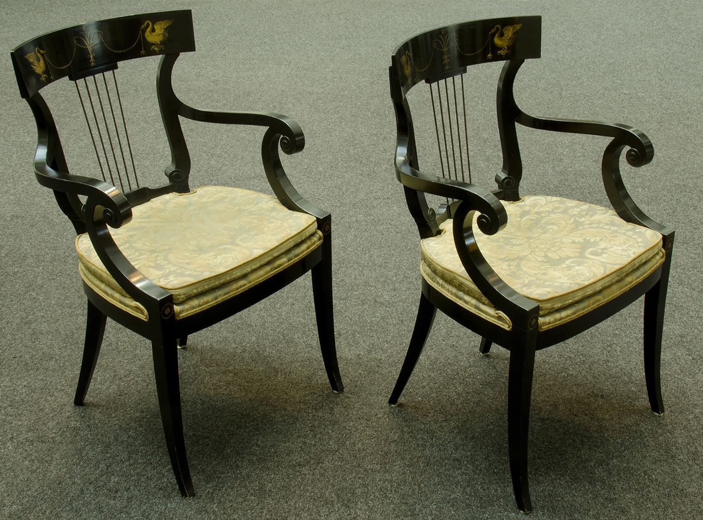 Pair curved back black lacquerarmchairs. decorated with