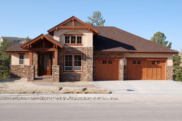 Exterior With Brown Stone Tan Stucco Wood Garage Doors