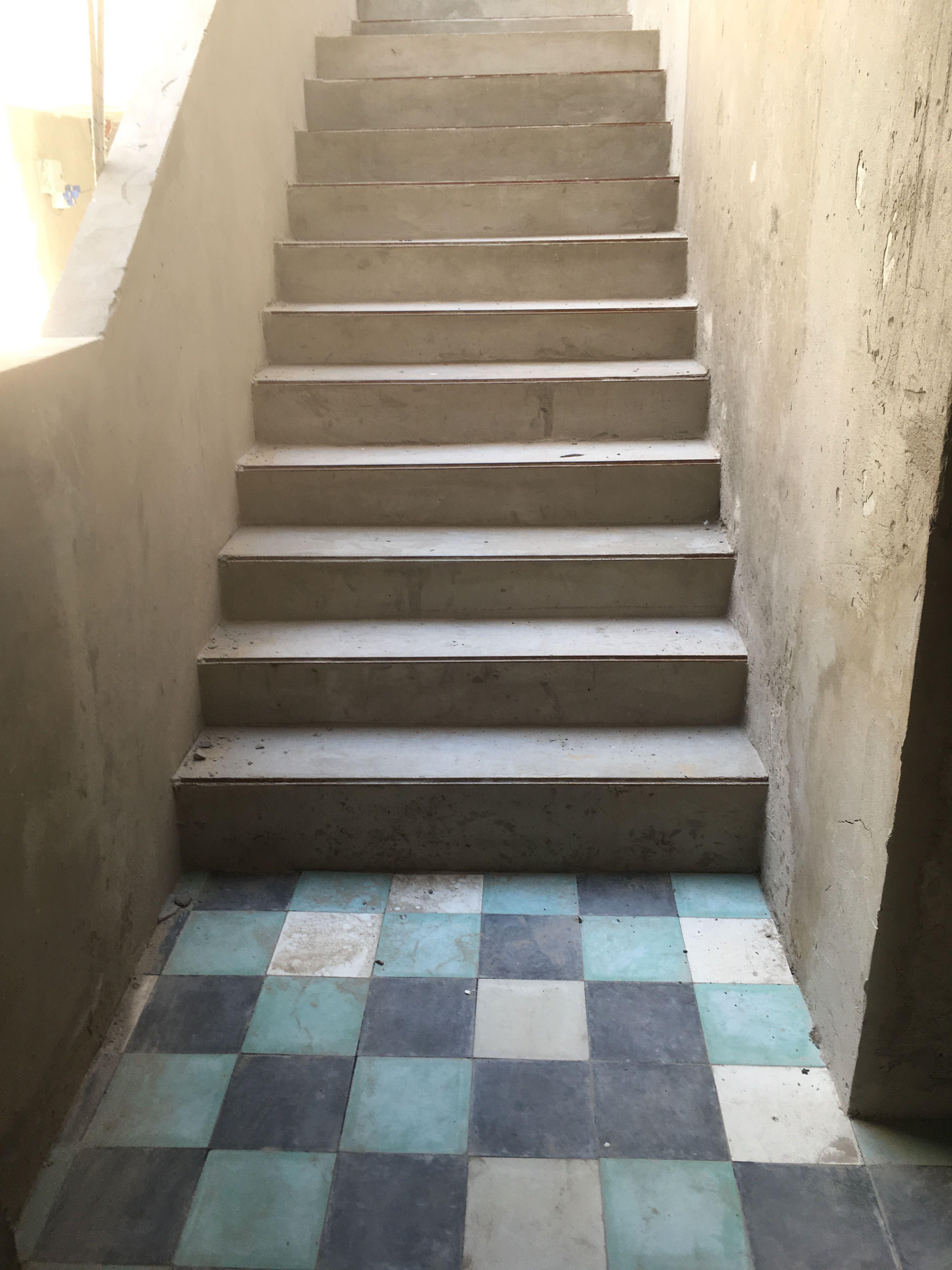 Escalera semicubierta, acceso desde la planta baja, hall edificio de viviendas de baja escala, con pisos calcáreos de 20x20, en color gris, crudo y esmeralda.  Arq. Estefanía Capatto