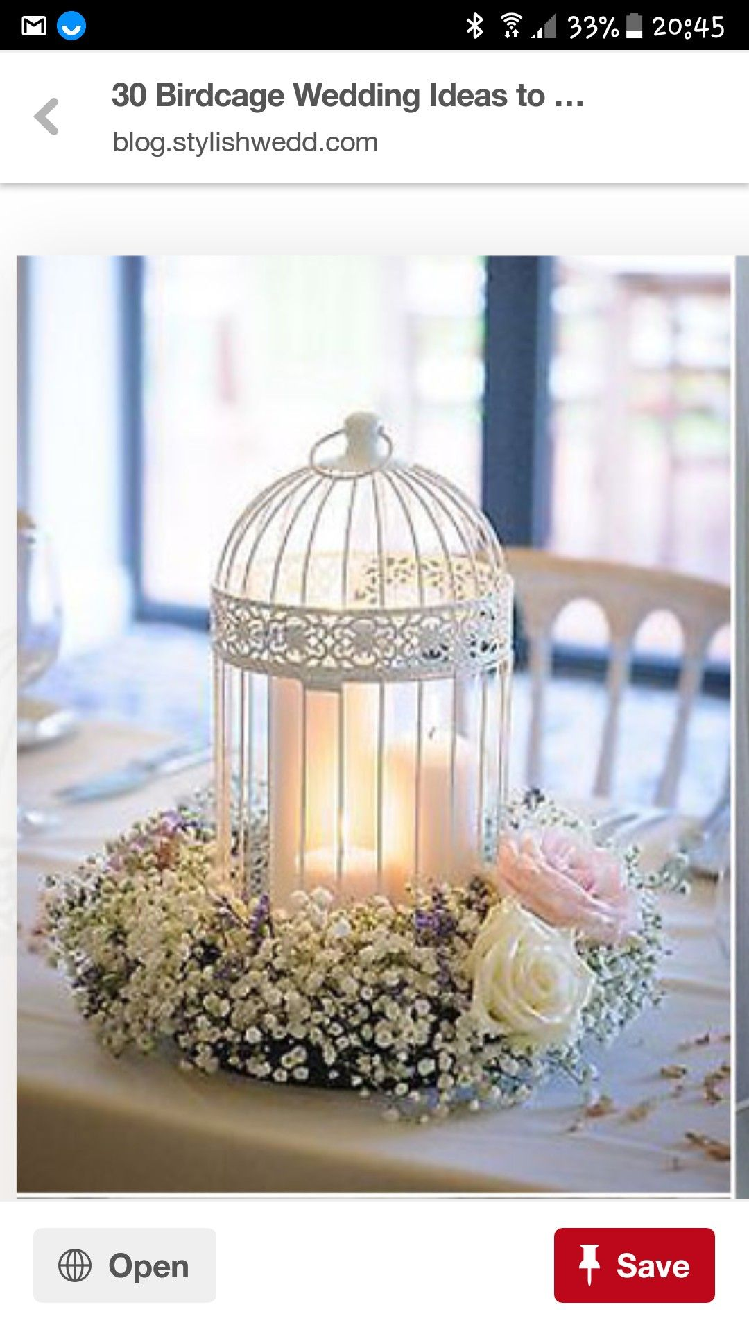 Pretty wedding centrepiece. bird cage with candle and flowers around ...