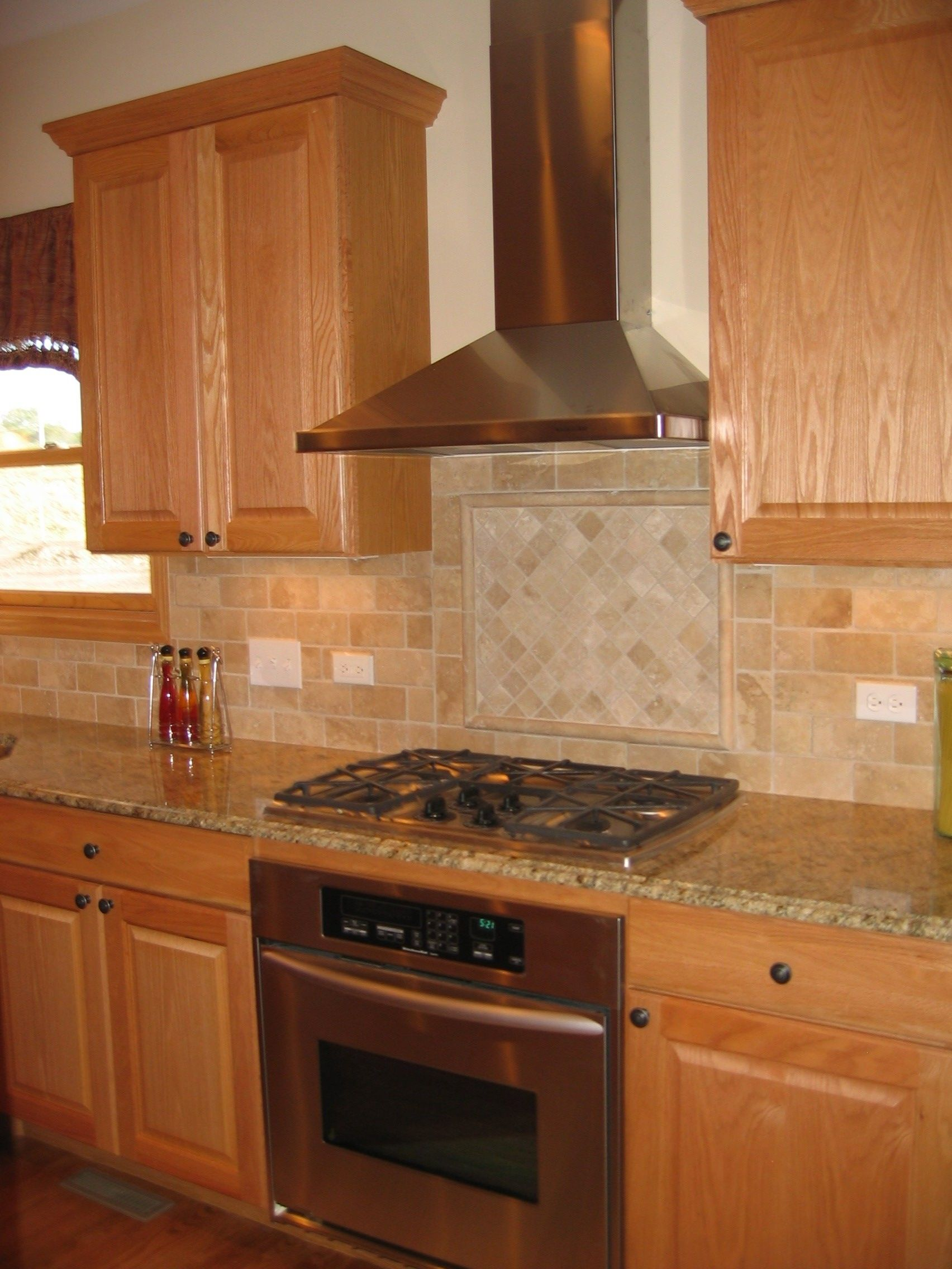 Kitchen with chimney hood. Tumbled Marble Backsplash with inlay ...