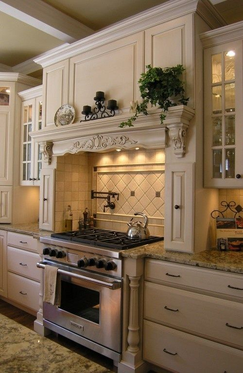 Kitchen decor · french detail mantle and glass cabinetry interior lighting