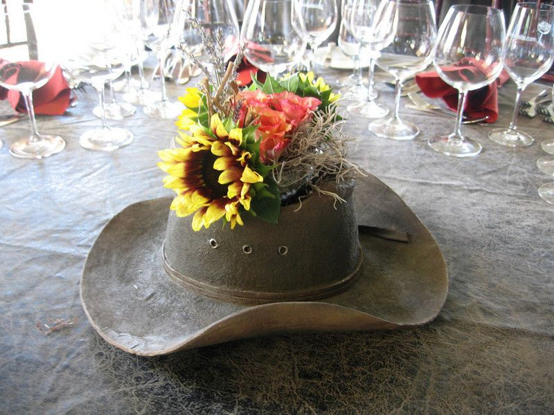 western wedding ideas use a cowboy hat as a vase for your reception table centerpiece flowers kinda cute maybe for gift table if you go barn