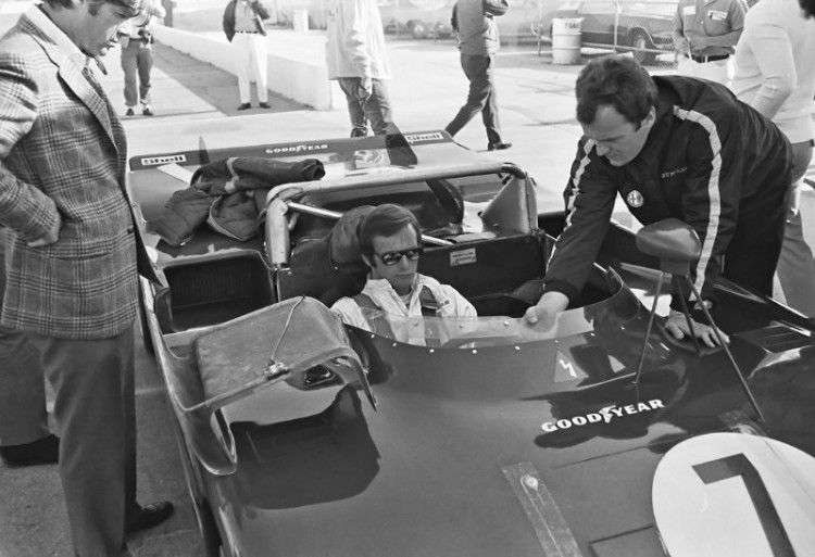 """Peter Revson being """"fitted"""" for his #7 Alfa Romeo 33/TT/3. Autodelta technical manager Gherardo Severi (far right) is explaining a few things to Revson. (Photo by Lou Galanos)"""