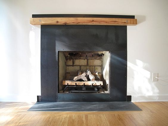 custom steel fireplace surround with heart pine mantel and stainless steel details