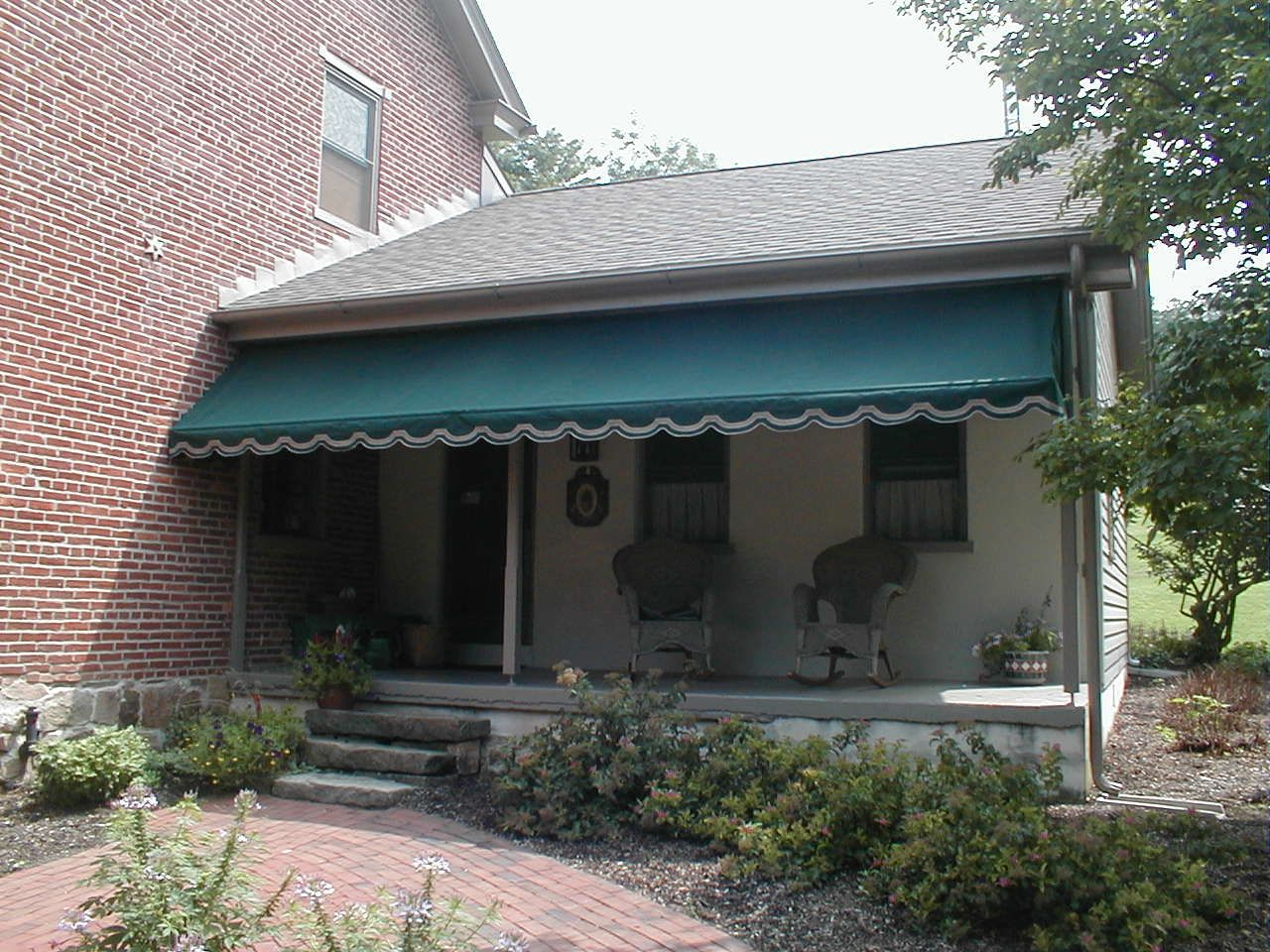 a custom made porch awning using forest green sunbrella fabric