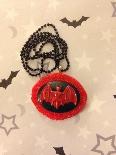 """Red bat cameo with a red filigree setting, on a 24"""" black ball chain necklace.  Pendant is approx. 1 3/4"""" by 2"""""""