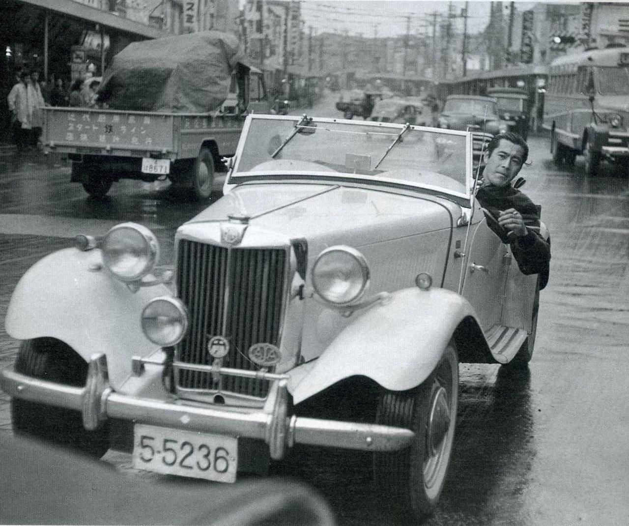Mifune Toshiro 三船敏郎 (1920-1997) driving his MG-TD in Shibuya 渋谷, Tokyo, Japan - 1958