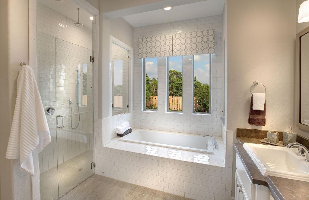 Tub built out with shower along side / glass window between the two