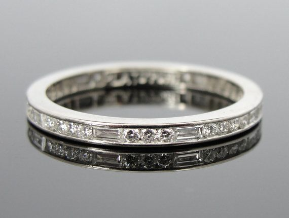 This vintage piece features beautiful baguette and round diamonds in a pretty pattern. This mix of rectangles and circles is a nice, geometric profile; slightly unusual and very sophisticated. The glittering stones continue all the way around the band - a continuous circle representing eternity. Engraved around the edges, this is a lovely piece of workmanship from the Art Deco Era. Metal: Platinum  Stones: 9 baguette diamond, totaling .32 carat, 27 round diamonds totaling .40 carat, F color…