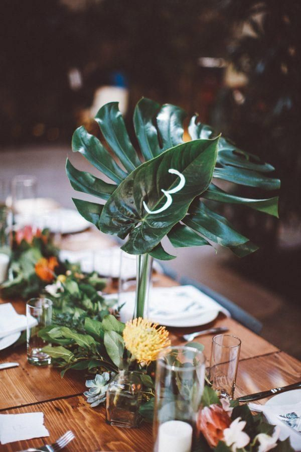 These hand-painted tropical frond escort number centerpieces are stunning! | Image by Katie Hoss