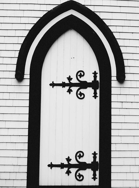 White arched door with black trim - Lunenburg, Nova Scotia