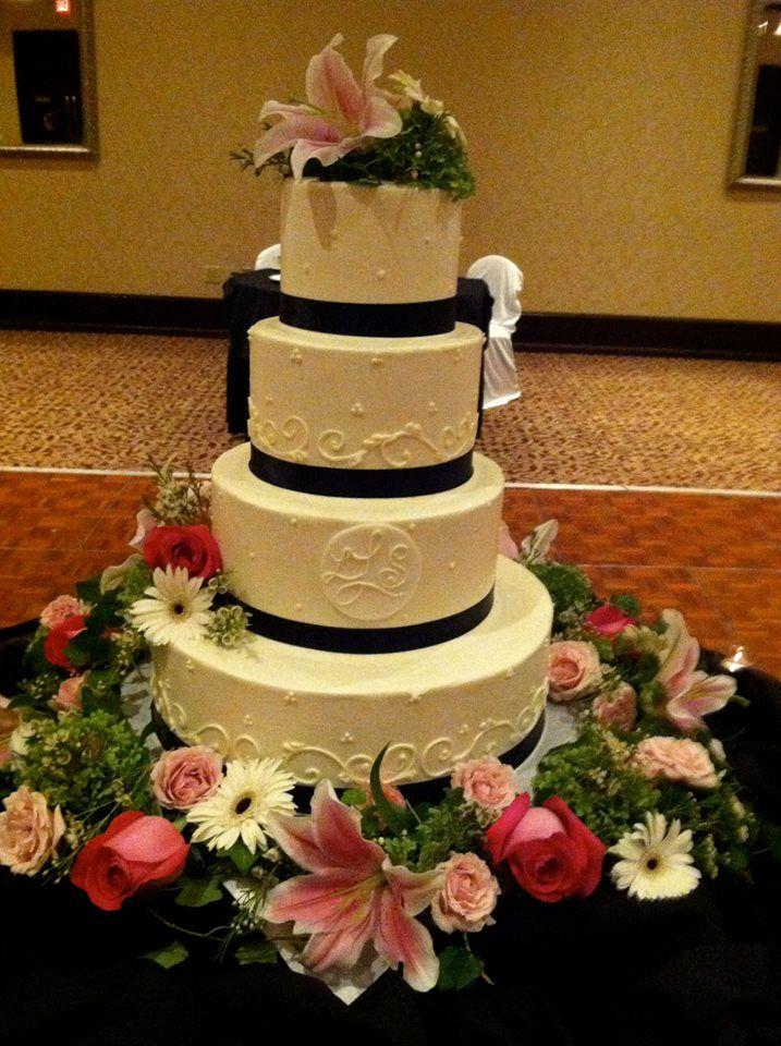 Black & white round cake with monogram & fresh floral.