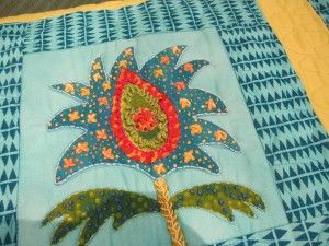 A block from the panel from our Folkloric Blooms fabrics embroidered and made into a quilt