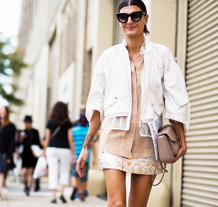 White jacket, tan blouse, printed mini skirt, and cat eye sunglasses