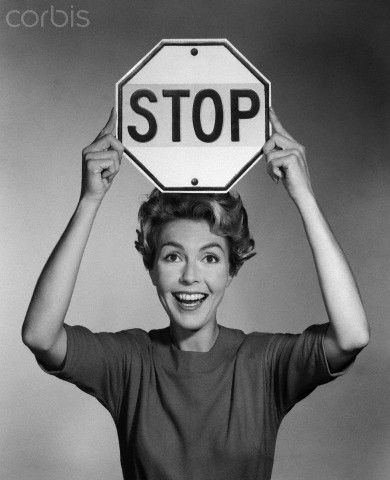 1950s 1960s smiling woman holding stop sign above her head looking at camera