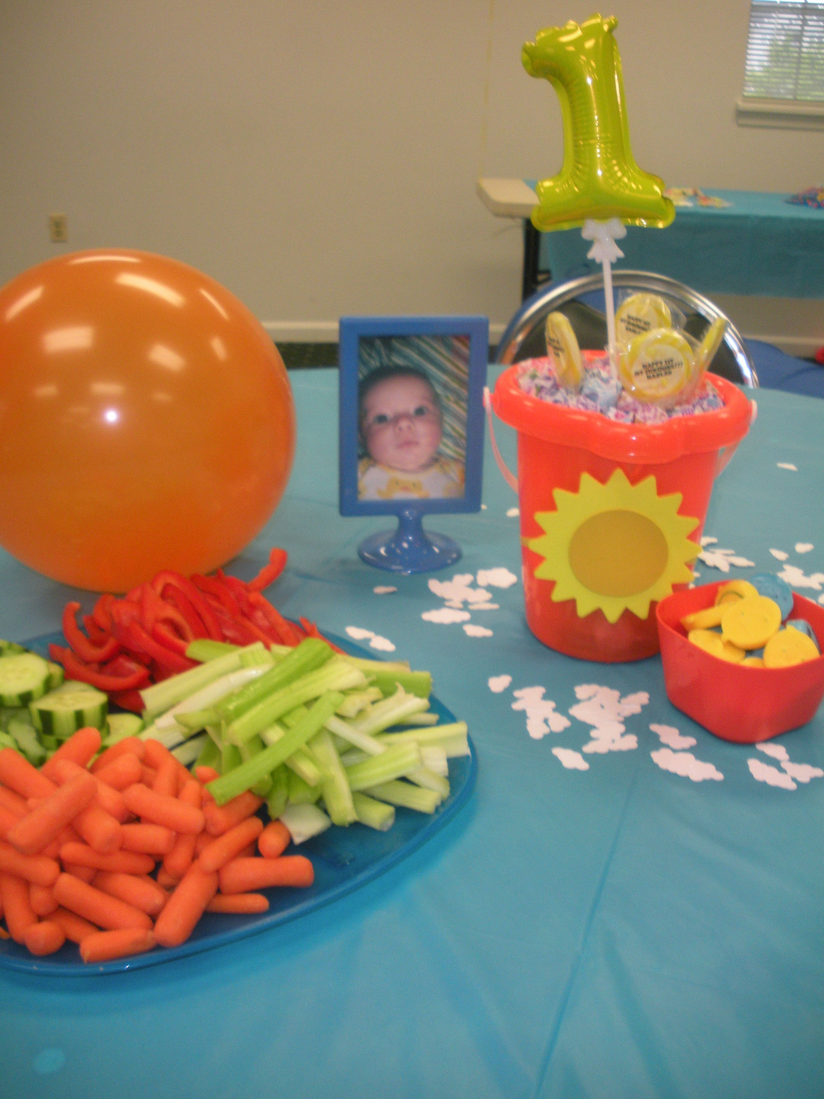 Center piece buckets with wood sun hot glued with ribbon.  1 balloon with lolipops stuck in foam.  Double sided frame from IKEA and smiley chocolate molds.  punched cloud confetti on blue table cloth