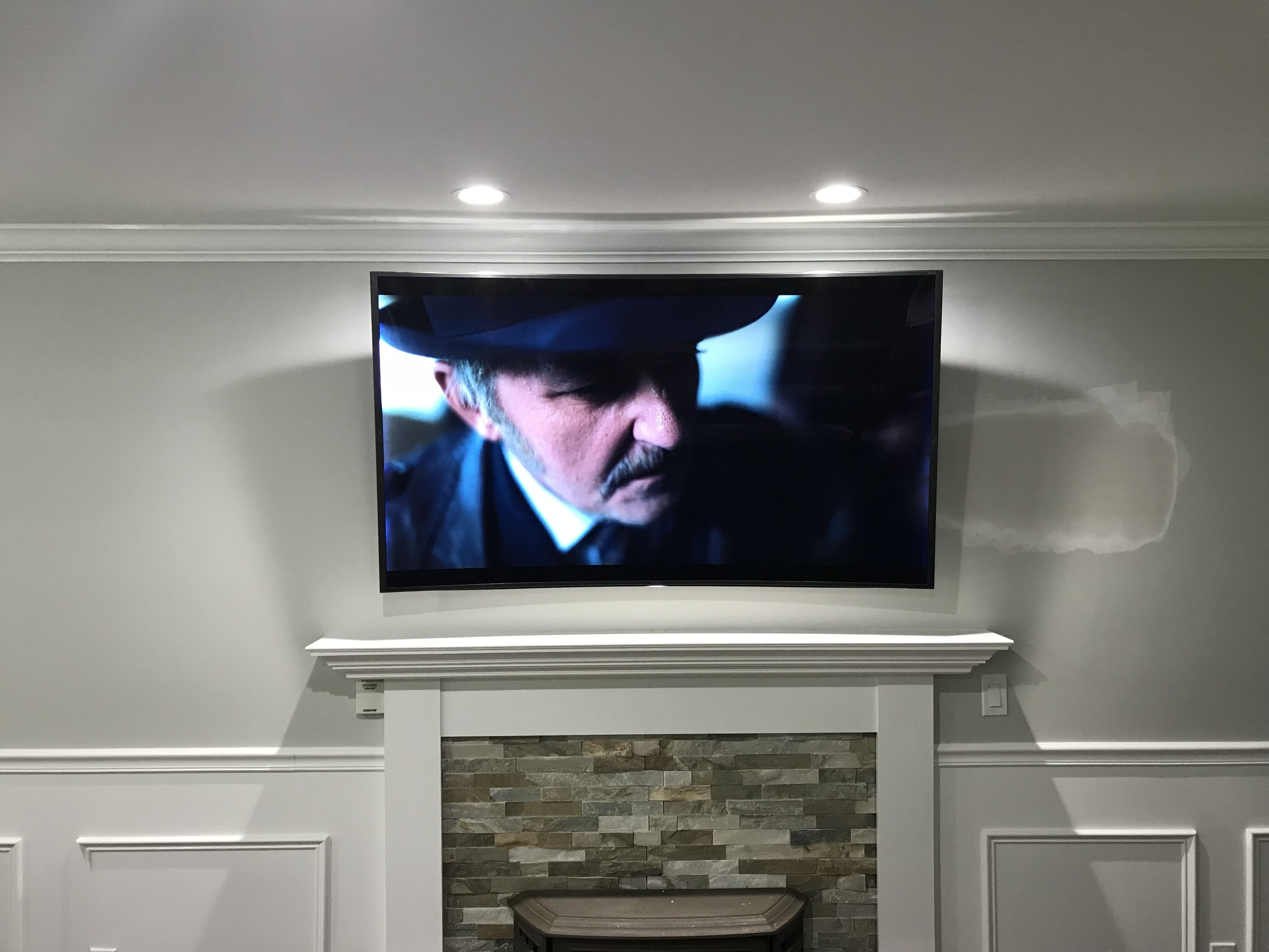 Curved Tv Mounted Over Fireplace With New Outlet Added And Wires