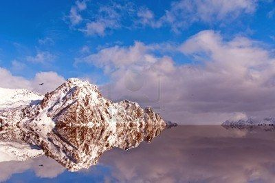 Reflections of the snowy mountains in the Arctic Circle on a sunny day and colorful winter