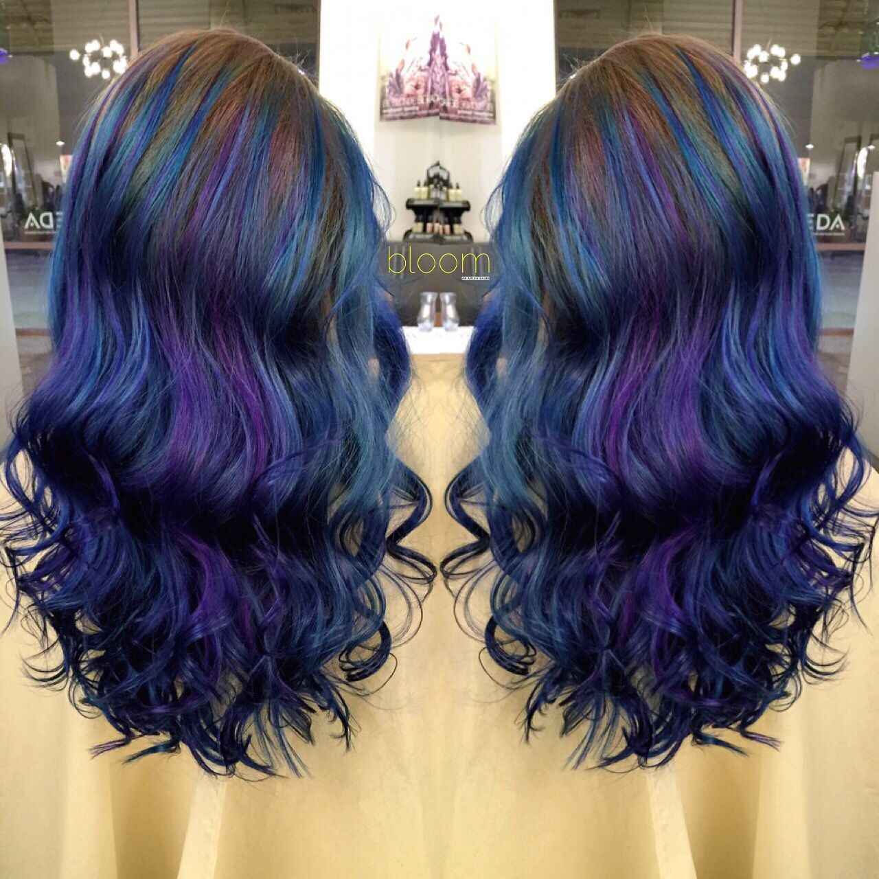 Violet and blue vivid hair color on long layered hair by bloom