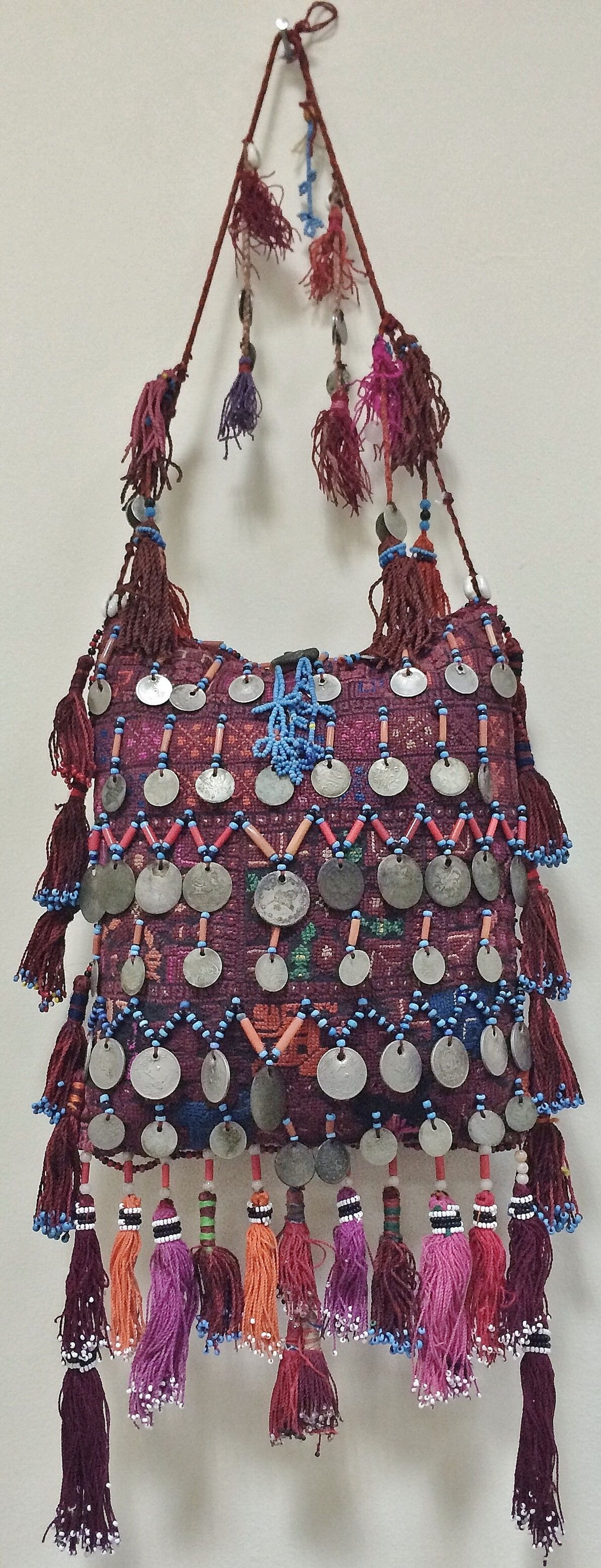 Large pouch with kohl container.  From Bersheeba (Palestine), 20th century.  Both sides are fully embroidered and adorned with coral- & glass beads, silk tassels, and antique coins (late-Ottoman and others).  (Source: Peter Hoesli).