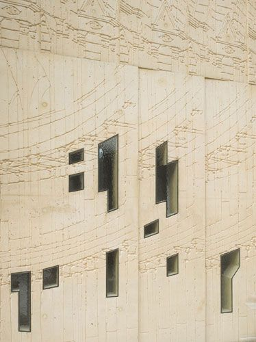 Tchoban Foundation Museum for Architectural Drawing (Berlin) by SPEECH Tchoban & Kuznetsov:  a close-up of the ground-level facade reveals delicately scribed concrete punctuated by a mottled glass fenestration.