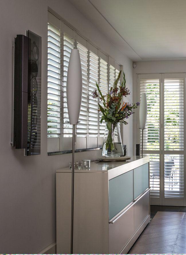 De ramen in de eetkamer zijn voorzien van witte shutters. Doordat de ...