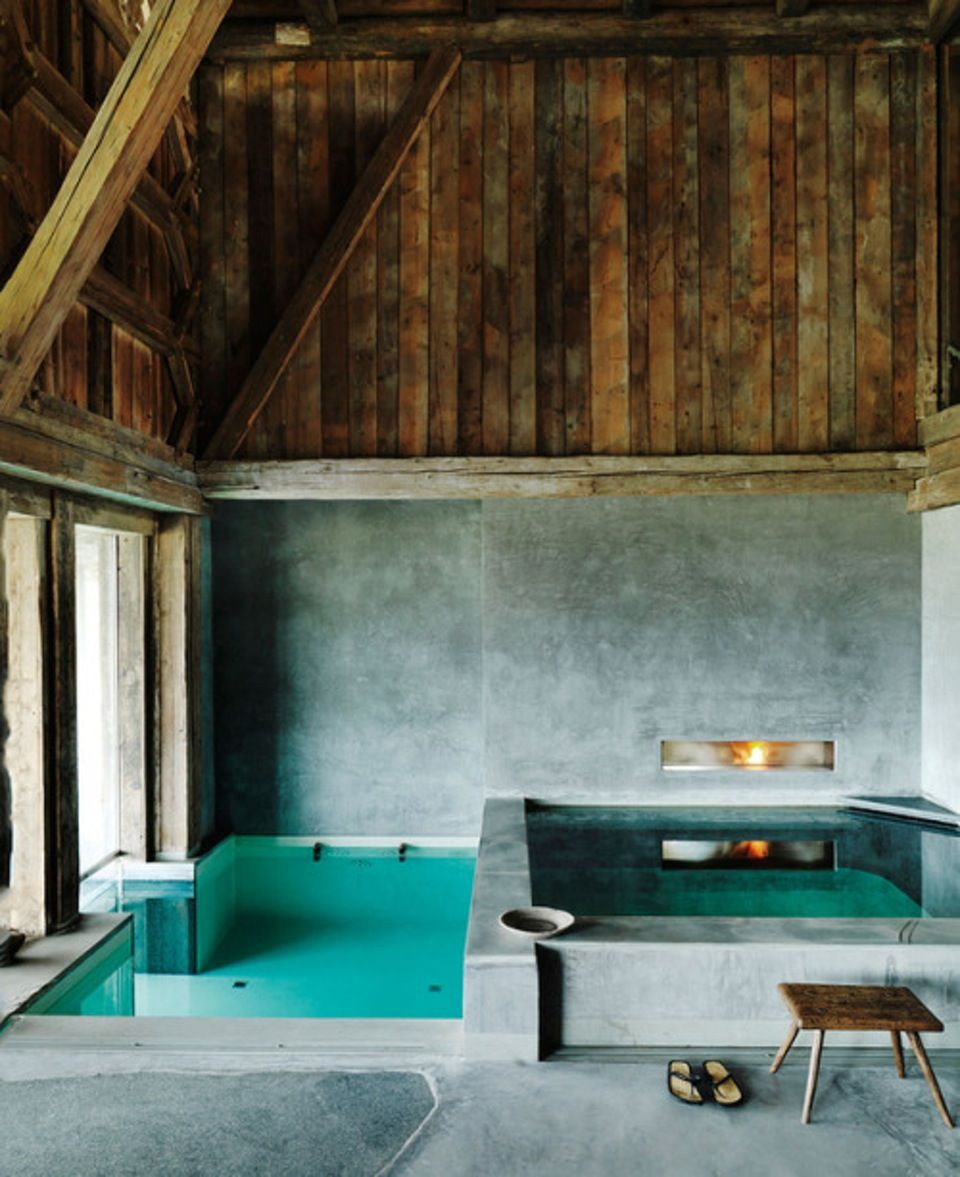 Rustic indoor swimming pool area in concrete and wood.