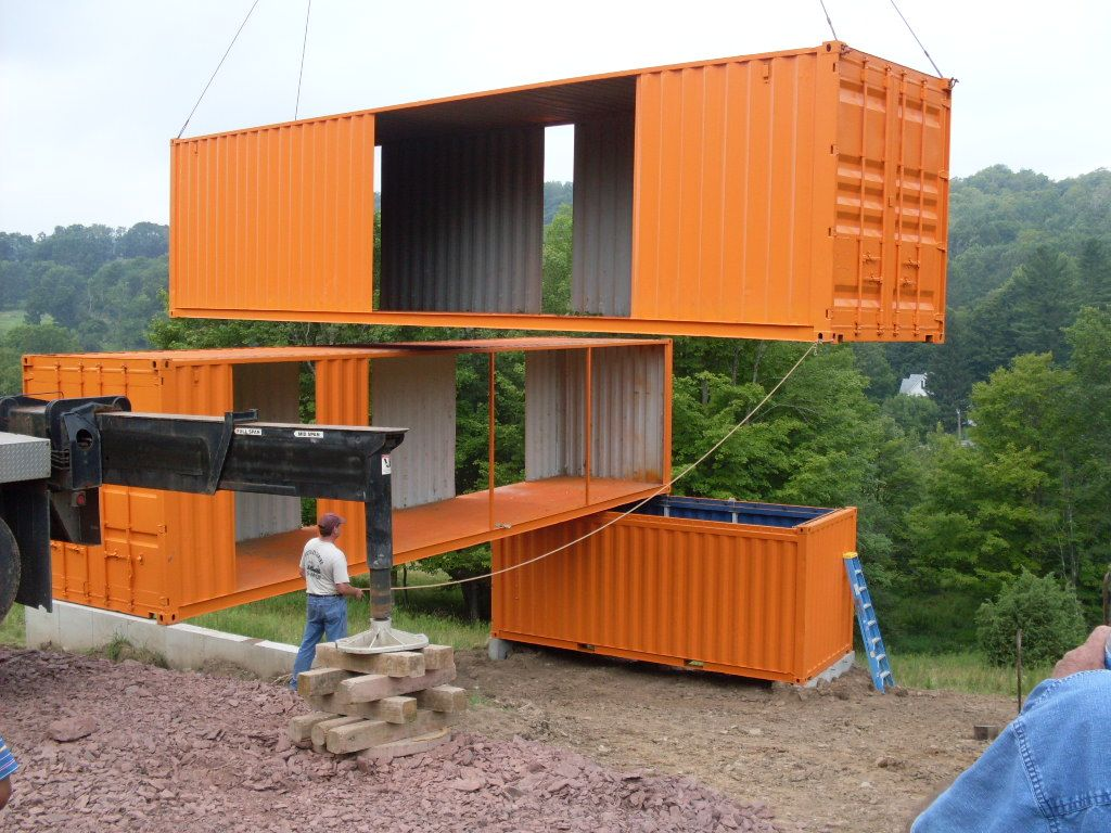 Cranes positioning a house made of recycled shipping for Cargo home designs