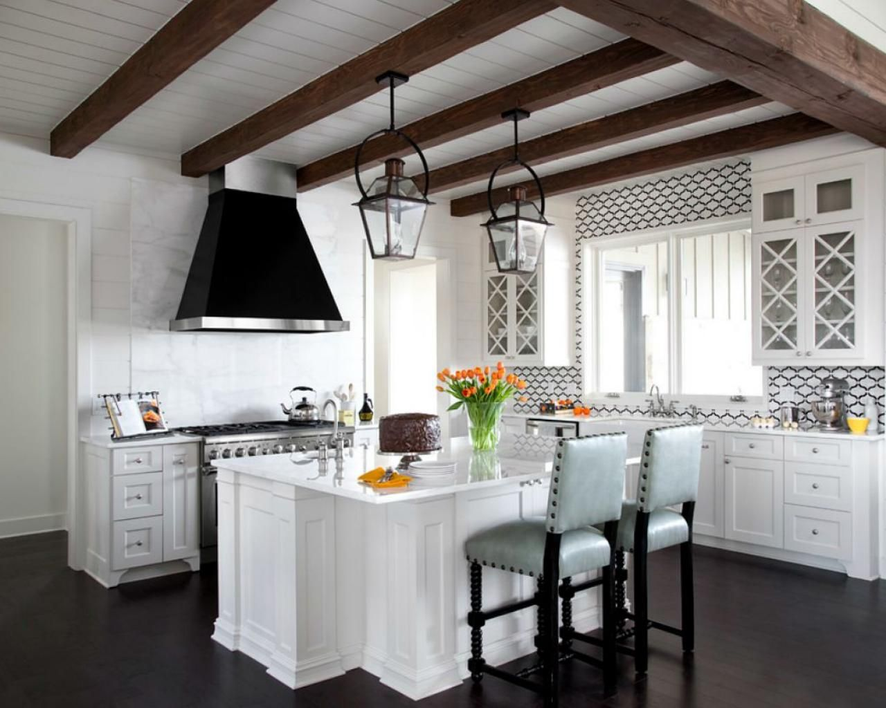 The kitchen is bright and fresh, with white cabinets and calacatta ...