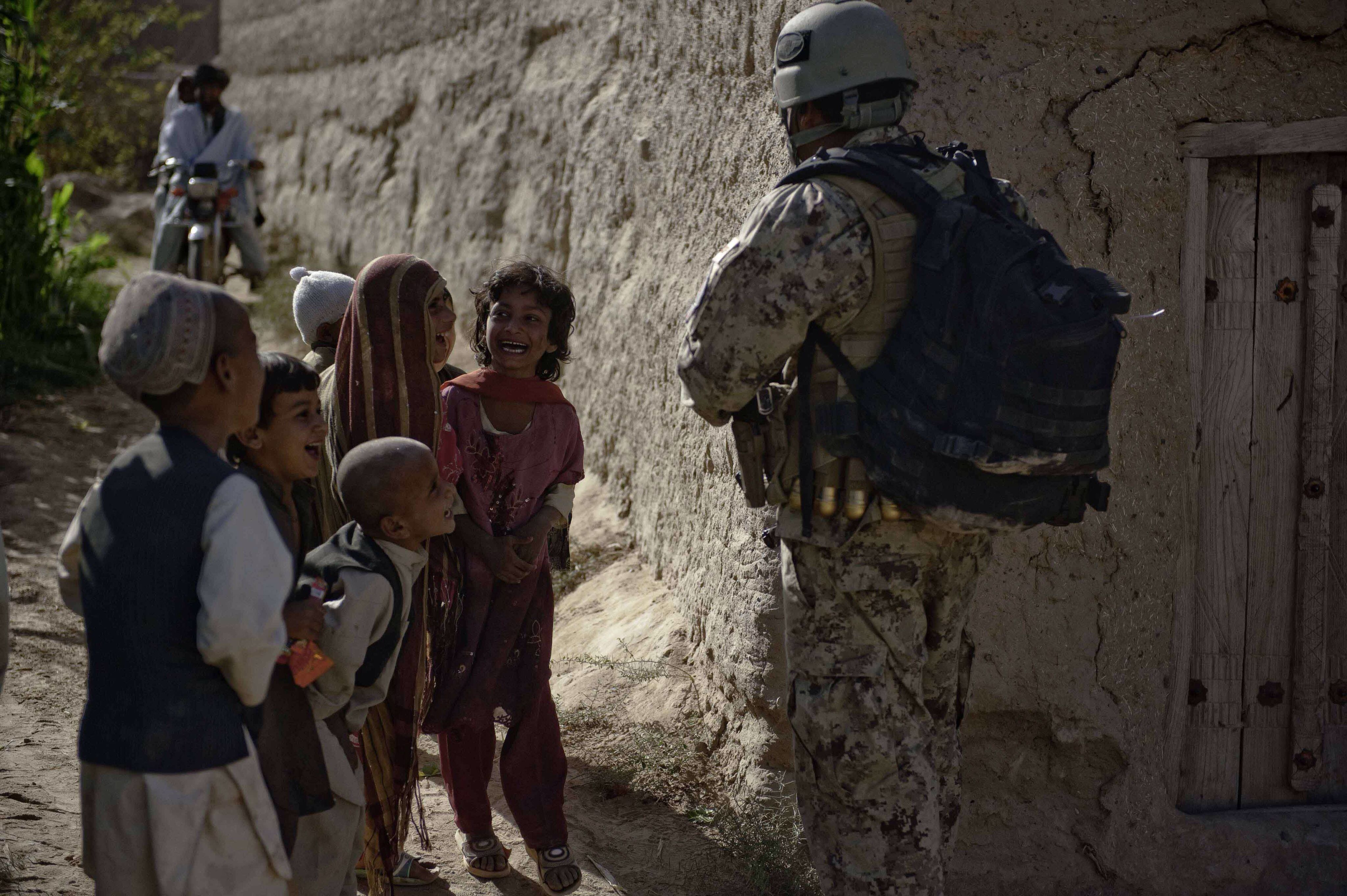 A U.S. Army Special Forces soldier entertains children in the Zhari district of Kandahar province while on a joint patrol, Oct. 19, 2010. (U.S. Army photo by Sgt. Ben Watson, Special Operations Task Force – South)