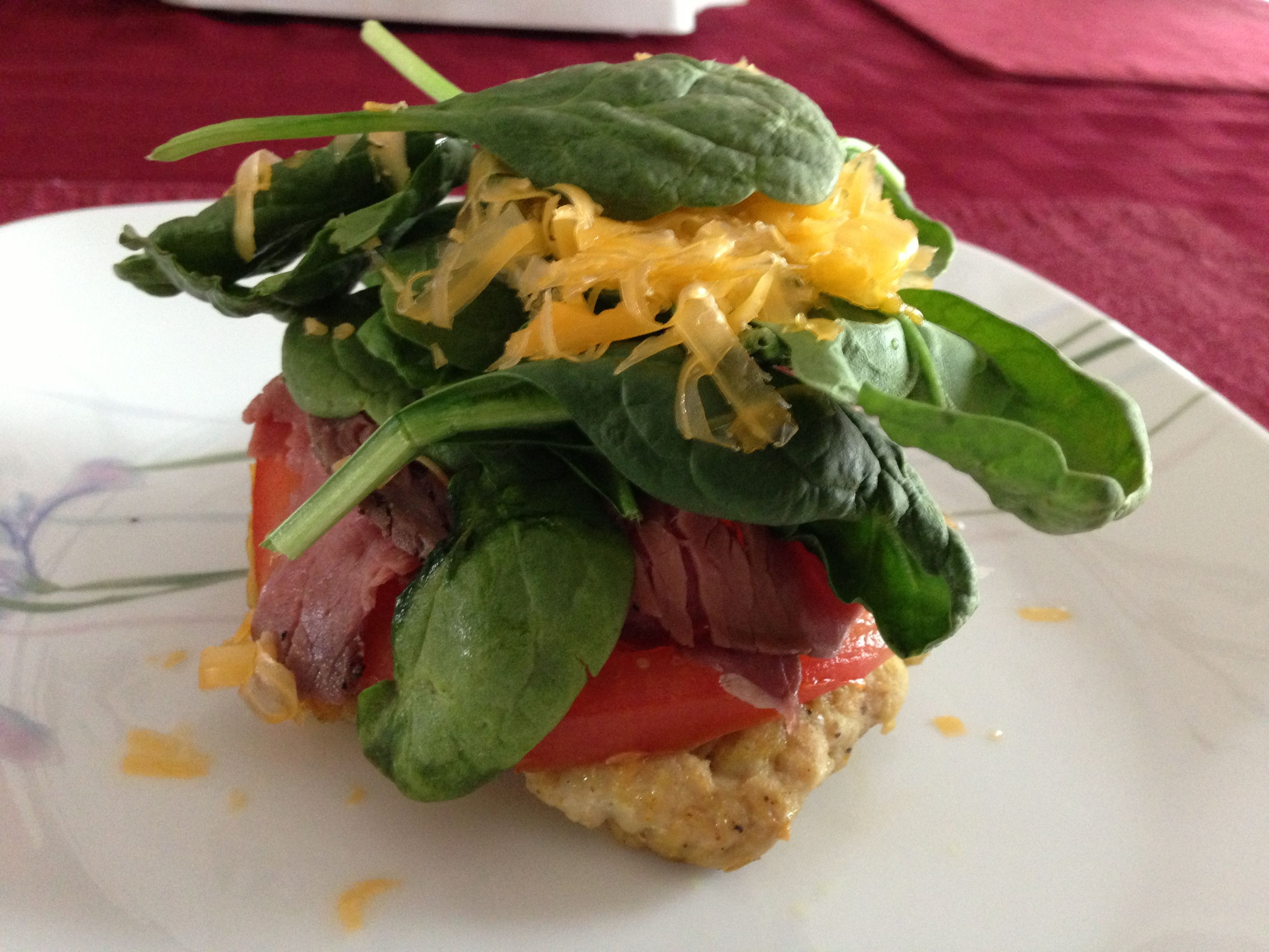 Turkey burger Toppings: Tomato, roast beef, avocado, spinach, cheddar cheese, and mustard.